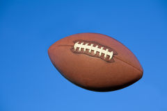 Fútbol americano en cielo azul con el camino de recortes. Foto de archivo libre de regalías