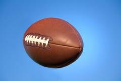 Fútbol americano en cielo azul con el camino de recortes. Fotografía de archivo