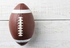 Fútbol americano en la tabla de madera blanca Imágenes de archivo libres de regalías