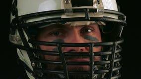 Fútbol americano Primer del jugador de fútbol americano en el casco que mira en cámara Mirada confiada de un americano almacen de metraje de vídeo