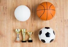 Fútbol, baloncesto, bolas del voleibol y tazas imagenes de archivo