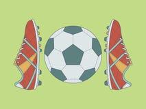 Fútbol/botas y balón de fútbol con contorno en fondo verde Fotografía de archivo