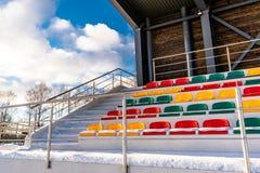 Fútbol colorido vacío y x28; Soccer& x29; Asientos del estadio en el invierno cubierto en la nieve - Sunny Winter Day imágenes de archivo libres de regalías