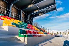 Fútbol colorido vacío y x28; Soccer& x29; Asientos del estadio en el invierno cubierto en la nieve - Sunny Winter Day imagen de archivo libre de regalías