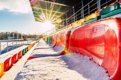 Fútbol colorido vacío y x28; Soccer& x29; Asientos del estadio en el invierno cubierto en la nieve - Sunny Winter Day con la llam imagenes de archivo
