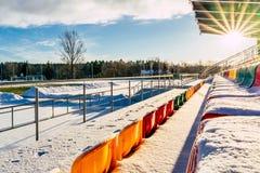 Fútbol colorido vacío y x28; Soccer& x29; Asientos del estadio en el invierno cubierto en la nieve - Sunny Winter Day con la llam imagen de archivo