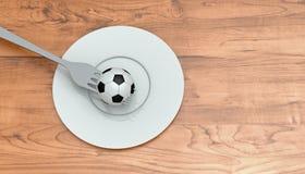 Fútbol como comida: fútbol, bifurcación y placa en una tabla de madera Imagenes de archivo