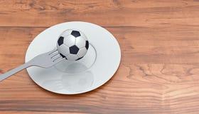 Fútbol como comida: fútbol, bifurcación y placa en una tabla de madera Imágenes de archivo libres de regalías