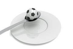 Fútbol como comida: fútbol, cuchara y placa Imagenes de archivo
