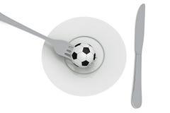Fútbol como comida: fútbol, placa y cubiertos Fotos de archivo libres de regalías