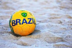 Fútbol con la bandera del Brasil en la playa de Copacabana Imágenes de archivo libres de regalías