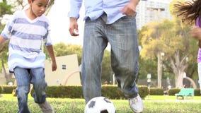 Fútbol de With Children Playing del padre en parque junto almacen de metraje de vídeo