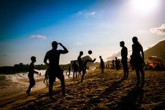 Fútbol de la playa por puesta del sol Fotos de archivo