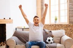 Fútbol de observación del adolescente feliz en casa Foto de archivo libre de regalías