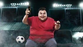 Fútbol de observación del hombre feliz y gordo de la diversión del fútbol - en el stadion, tomando la cerveza y el balón de fútbo Imagen de archivo libre de regalías
