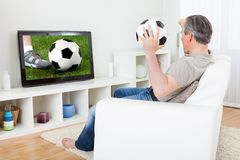 Fútbol de observación del hombre maduro en la televisión fotos de archivo libres de regalías
