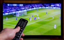 Fútbol de observación en la TV y usar el control remoto foto de archivo libre de regalías