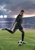Fútbol de retroceso con el pie del jugador de fútbol afroamericano joven imagen de archivo libre de regalías