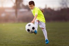 Fútbol de retroceso con el pie del muchacho en el campo de deportes Fotografía de archivo libre de regalías