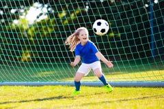 Fútbol del juego de los niños Niño en el campo de fútbol Imagen de archivo libre de regalías