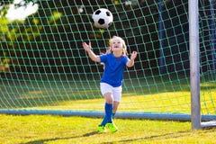 Fútbol del juego de los niños Niño en el campo de fútbol Imagenes de archivo