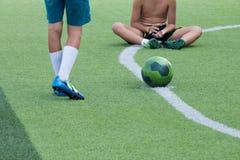 Fútbol del juego de niños en el césped Fotografía de archivo