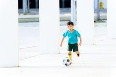 Fútbol del juego del muchacho debajo del edificio vacío Imagen de archivo