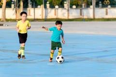 Fútbol del juego del muchacho en el piso concreto azul Fotos de archivo