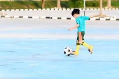 Fútbol del juego del muchacho en el piso concreto azul Fotografía de archivo
