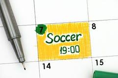 Fútbol 19-00 del recordatorio en calendario con la pluma verde Imagen de archivo