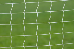 Fútbol detrás de la red de la meta Foto de archivo libre de regalías