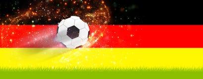 Fútbol en hierba delante de los colores de Alemania Imagenes de archivo