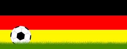 Fútbol en hierba delante de los colores de Alemania Foto de archivo libre de regalías