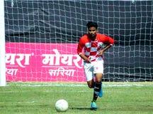 Fútbol/jugador de fútbol en la acción en la tierra verde fotografía de archivo