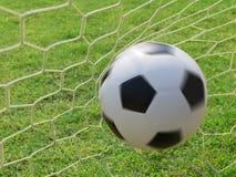 Fútbol que hace girar en meta en el campo de hierba verde Fotos de archivo
