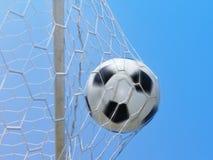 Fútbol que hace girar en meta y cielo azul Fotos de archivo libres de regalías