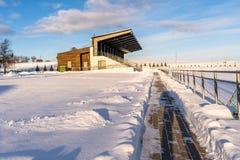 Fútbol vacío ( Soccer) Asientos del estadio en el invierno cubierto en parte en la nieve - Sunny Winter Day fotos de archivo