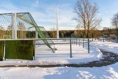 Fútbol vacío ( Soccer) Campo en el invierno cubierto en parte en la nieve - Sunny Winter Day foto de archivo