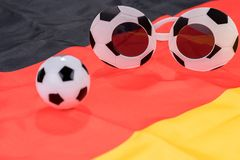 Fútbol y vidrios abstractos en la bandera alemana Fotos de archivo libres de regalías