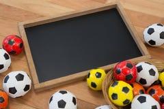 Fútboles coloridos y pizarra en la tabla de madera Fotografía de archivo