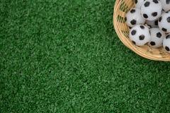 Fútboles en cesta de mimbre en hierba artificial Foto de archivo