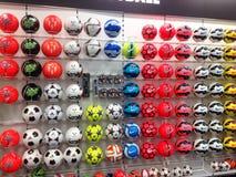 Fútboles o balones de fútbol en la exhibición en una tienda de los deportes Imágenes de archivo libres de regalías