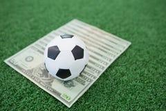 Fútboles y notas de la moneda sobre hierba artificial Fotos de archivo
