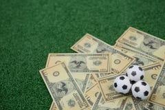 Fútboles y notas de la moneda sobre hierba artificial Imagenes de archivo