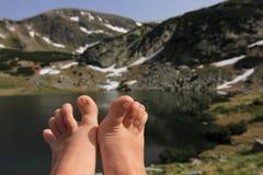 Füße über Gebirgssee Stockbild