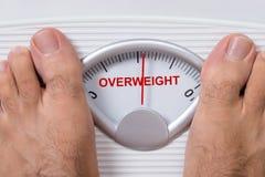 Füße auf der Gewichtsskala, die Übergewicht anzeigt Lizenzfreies Stockbild