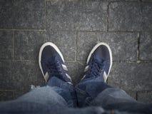 Füße auf der Pflasterung Stockfoto