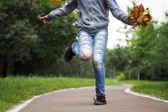 Füße auf der Straße Zerrissene Jeans, ein Tanz, ein Blumenstrauß des Herbstlaubs Lizenzfreie Stockbilder