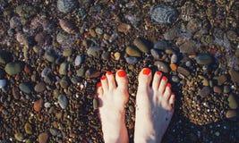 Füße auf einem Pebble Beach stockbilder