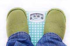 Füße auf einer Badezimmerskala, die Gewicht zeigt Stockbilder